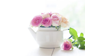 Bouquet of yellow and pink roses in a white enameled vintage teapot in bright sunlight on a white wooden table, rustic home decoration background