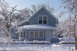 Snow and ice covered house after ice storm and blizzard, blue and white.