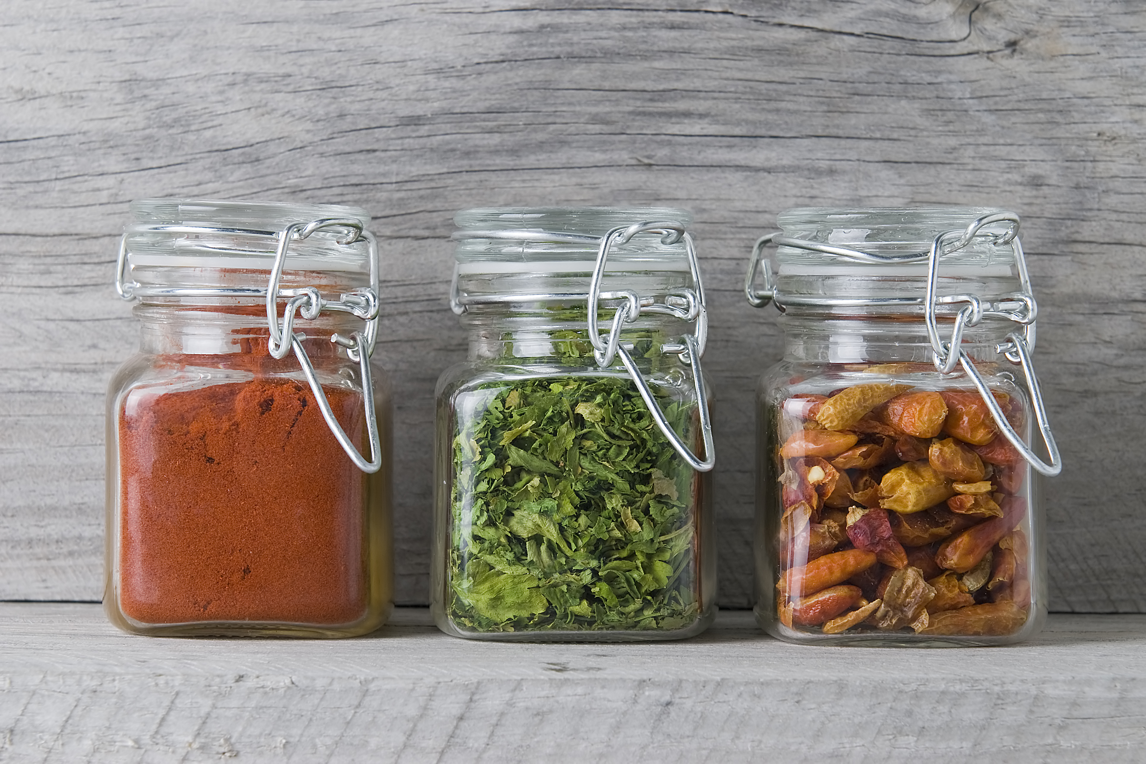 Three jars with paprika, parsley and chilli on an old wooden spice rack.