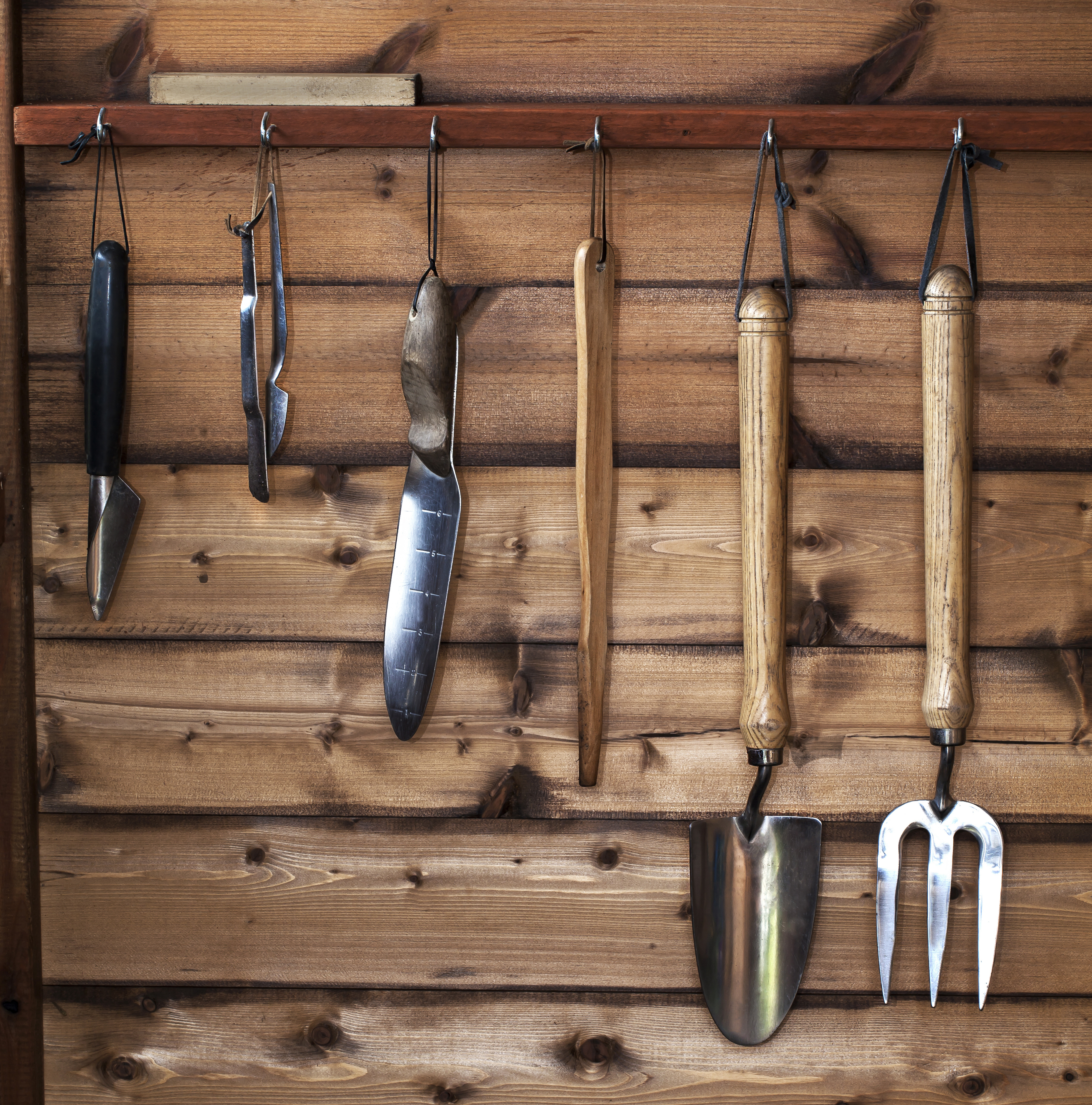 Assorted garden tools hanging up in wooden shed, dibbers, trowel, fork and spade.