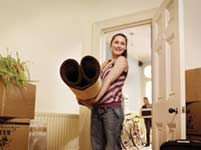 Woman holding a carpet while moving house