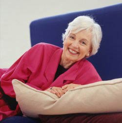 A senior citizen on a sofa smiling